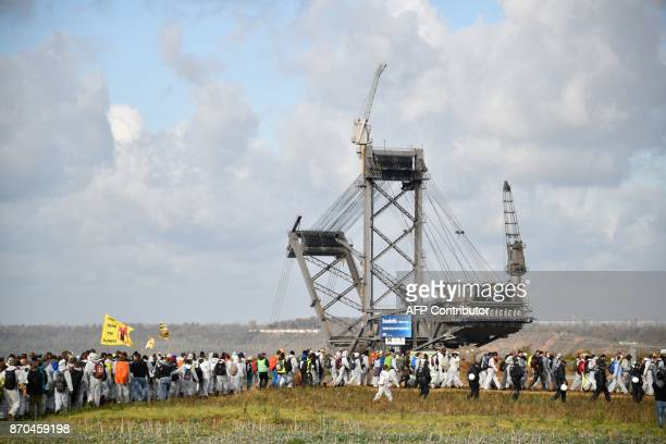 Environmentalists march past a giant bucketwheel excavator of the Hambach lignite open pit mine near Elsdorf western Germany on November 5 during a...