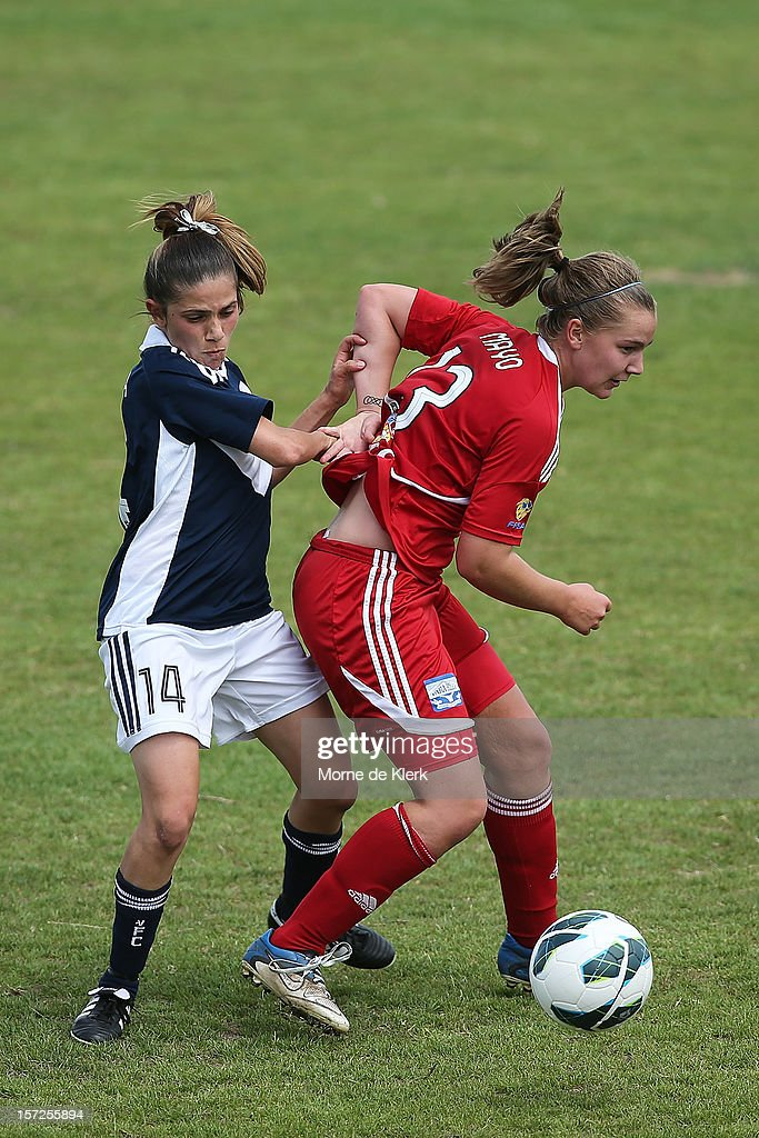 Enza Barilla (L) of Melbourne competes with Ann Mayo of Adelaide during the round seven W-League match between Adelaide United and the Melbourne Victory at Burton Park on December 1, 2012 in Adelaide, Australia.