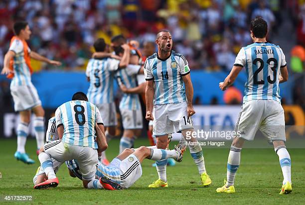 Enzo Perez Martin Demichelis Javier Mascherano and Jose Maria Basanta of Argentina celebrate after defeating Belgium 10 during the 2014 FIFA World...