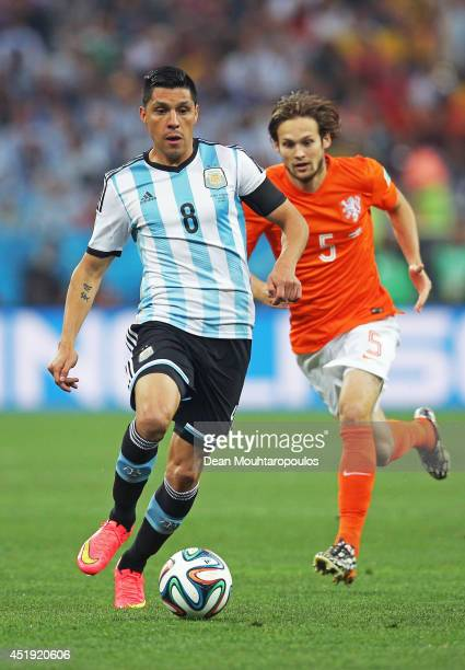 Enzo Perez of Argentina controls the ball against Daley Blind of the Netherlands during the 2014 FIFA World Cup Brazil Semi Final match between the...