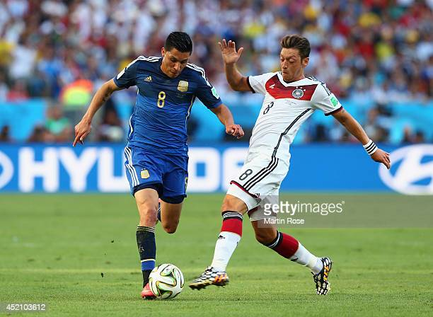 Enzo Perez of Argentina is challenged by Mesut Oezil of Germany during the 2014 FIFA World Cup Brazil Final match between Germany and Argentina at...