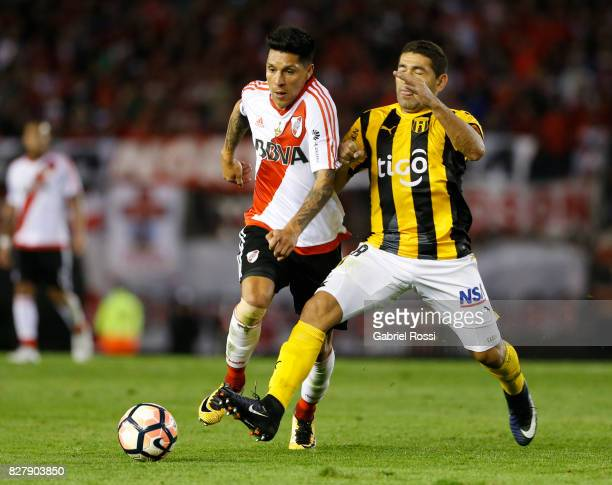 Enzo Perez of River Plate fights for the ball with Marcelo Palau of Guarani during a second leg match between River Plate and Guarani as part of...
