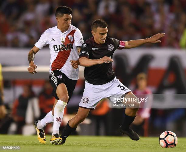 Enzo Perez of River Plate fights for the ball with Maximiliano Velazquez of Lanus during a first leg match between River Plate and Lanus as part of...