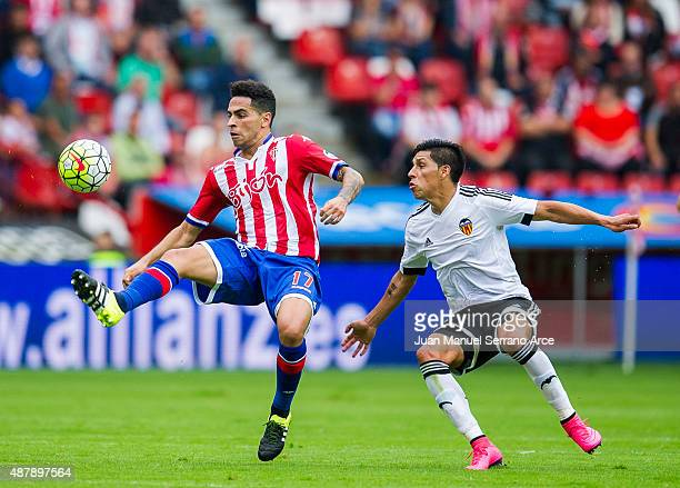 Enzo Perez of Valencia CF duels for the ball with Mascarell of Sporting Gijon during the La Liga match between Sporting Gijon and Valencia CF at...