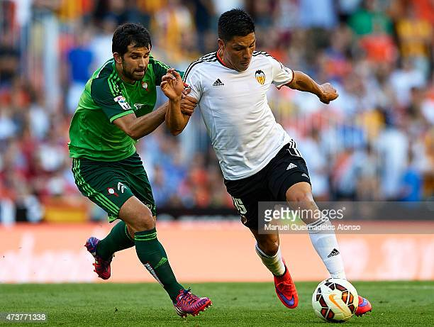 Enzo Perez of Valencia competes for the ball with Alex Lopez of Celta de Vigo during the La Liga match between Valencia CF and Celta de Vigo at...