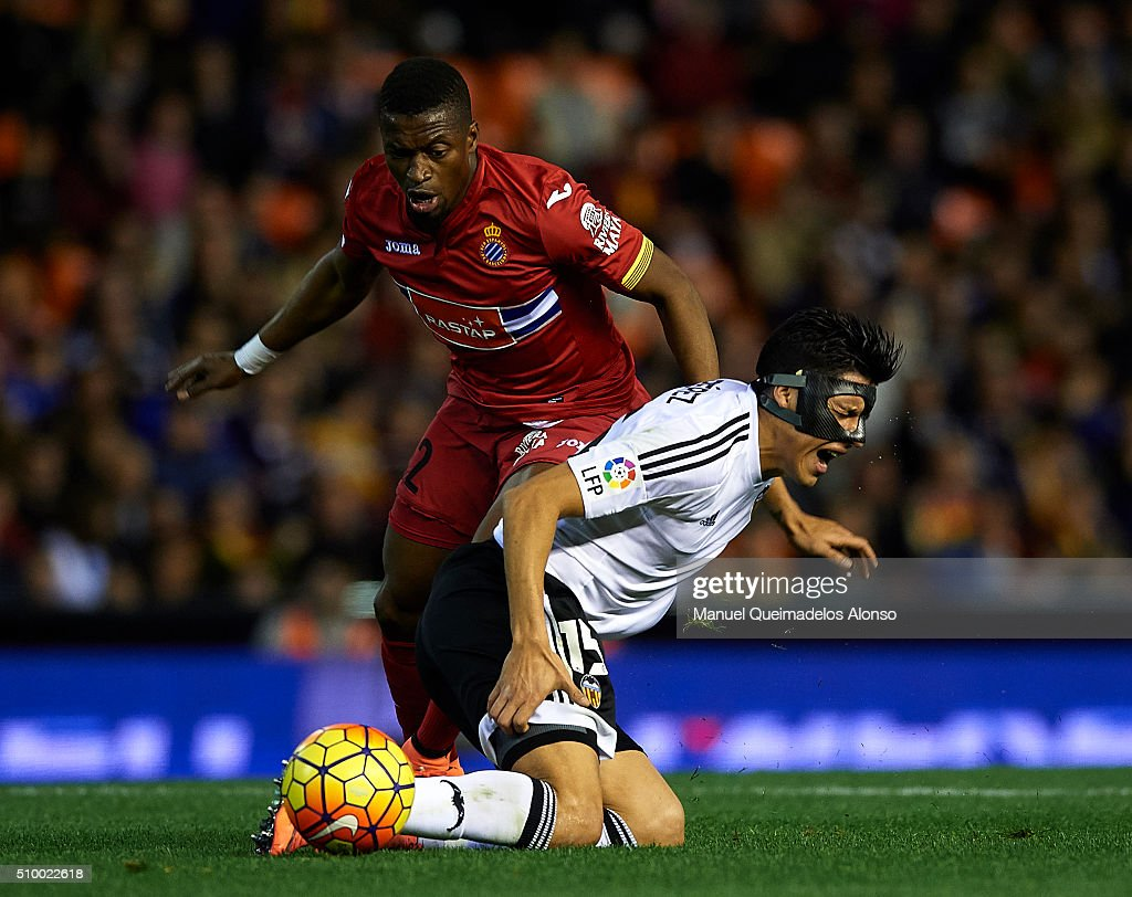 Enzo Perez (R) of Valencia is tackled by Papakouly Diop of Espanyol during the La Liga match between Valencia CF and RCD Espanyol at Estadi de Mestalla on February 13, 2016 in Valencia, Spain.