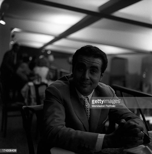 Enzo Tortora the Italian television anchorman is sitting in a nightclub at the Idroscalo raises his eyebrows and gives a little smile to the camera...