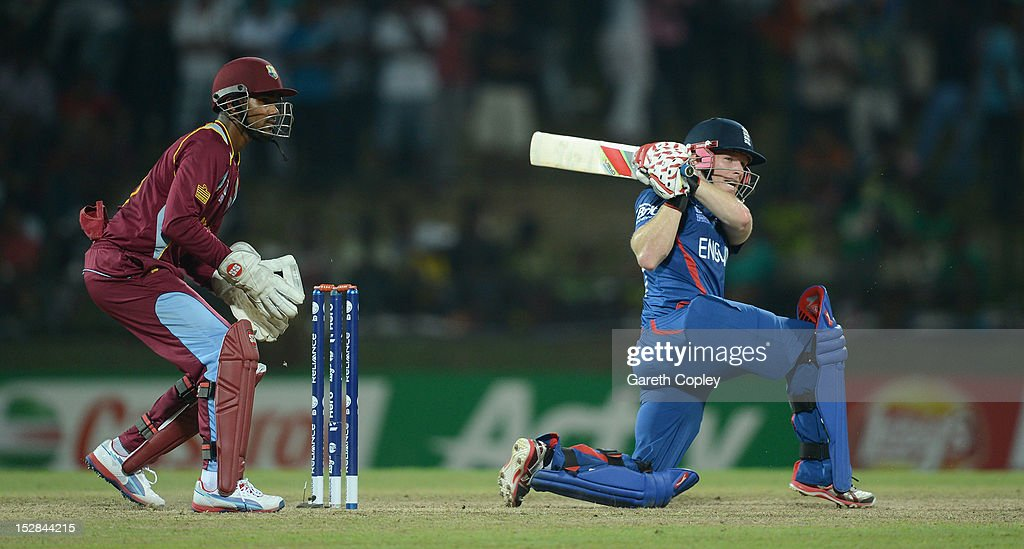 <a gi-track='captionPersonalityLinkClicked' href=/galleries/search?phrase=Eoin+Morgan&family=editorial&specificpeople=689581 ng-click='$event.stopPropagation()'>Eoin Morgan</a> of England hits out for six runs watched by West Indies wicketkeeper <a gi-track='captionPersonalityLinkClicked' href=/galleries/search?phrase=Denesh+Ramdin&family=editorial&specificpeople=542842 ng-click='$event.stopPropagation()'>Denesh Ramdin</a> during the ICC World Twenty20 2012 Super Eights Group 1 match between England and the West Indies at Pallekele Cricket Stadium on September 27, 2012 in Kandy, Sri Lanka.