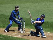 Eoin Morgan of England plays a shot as Sri Lnka wicketkeeper Kumar Sangakkara looks on during the 2015 ICC Cricket World Cup match between England...