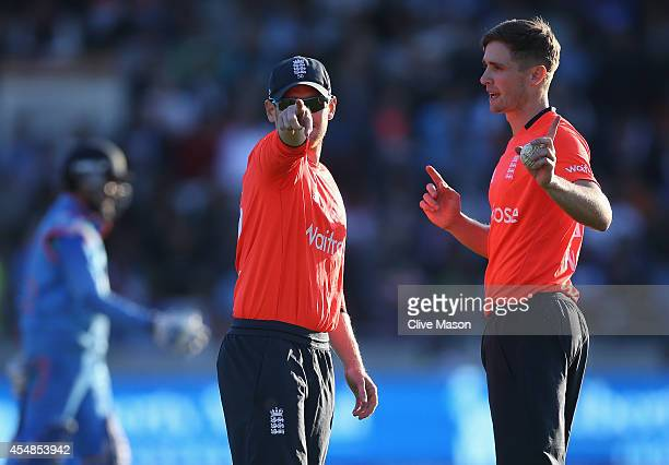 Eoin Morgan of England tals with Chris Woakes of England as he prepares to bowl the last ball during the NatWest International T20 2014 match between...