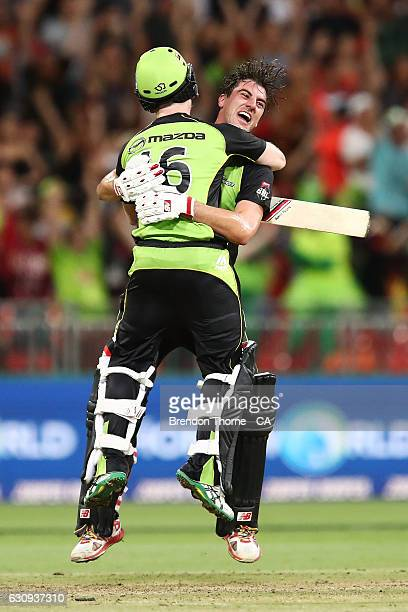 Eoin Morgan of the Thunder celebrates with team mate Pat Cummins after hitting a six off the last ball for victory over the Stars during the Big Bash...