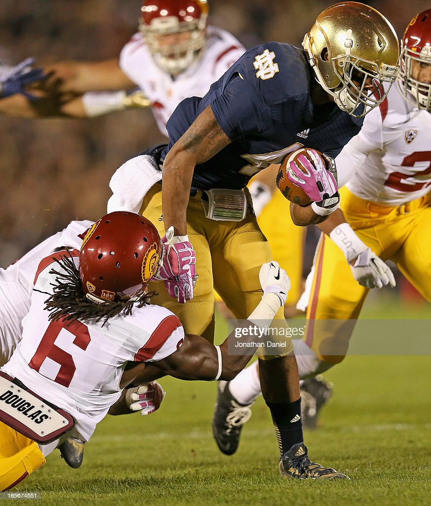 eorge Atkinson III #4 of the Notre Dame Fighting Irish is hit by Hayes Pullard #10 and Josh Shaw #6 of the University of Southern California Trojans at Notre Dame Stadium on October 19, 2013 in South Bend, Indiana. Notre Dame defeated USC