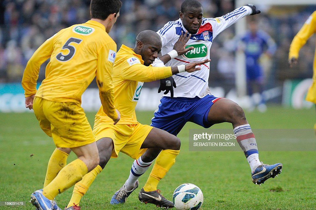 Epinal's French defender Aliou Dembele (C) vies with Lyon's French midfielder Gueida Fofana (R) during their French cup football match Epinal (SAS) versus Lyon (OL) at the Colombiere Stadium in Epinal, on January 6, 2013. AFP PHOTO / SEBASTIEN BOZON