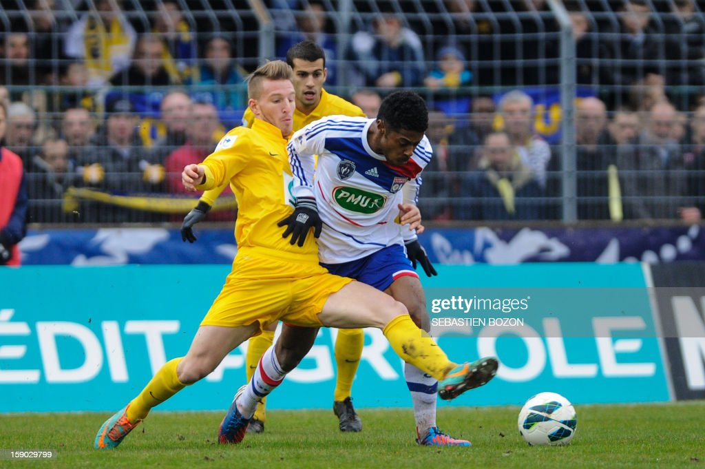 Epinal's French defender Judicael Crillon (L) vies with Lyon's Brazilian midfielder Michel Fernandes Bastos (C) during their French cup football match Epinal (SAS) versus Lyon (OL) at the Colombiere Stadium in Epinal, on January 6, 2013.