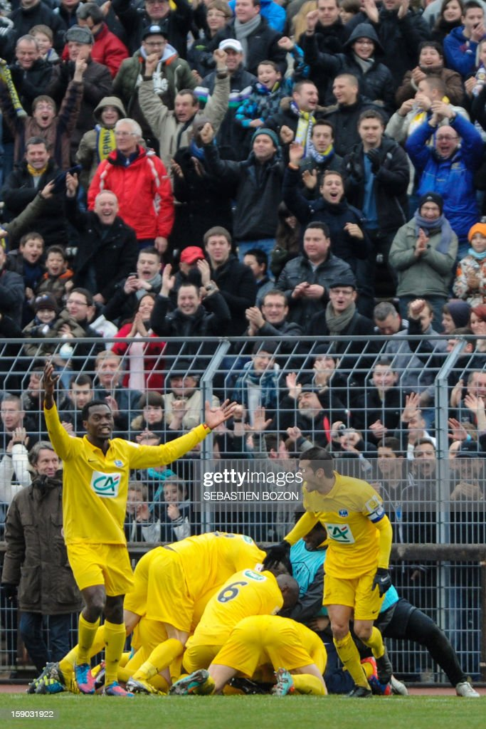 Epinal's French midfielder Tristan Boubaya (hidden) jubilates with teammates after scoring a goal during the French cup football match Epinal (SAS) versus Lyon (OL) at the Colombiere Stadium in Epinal, on January 6, 2013.