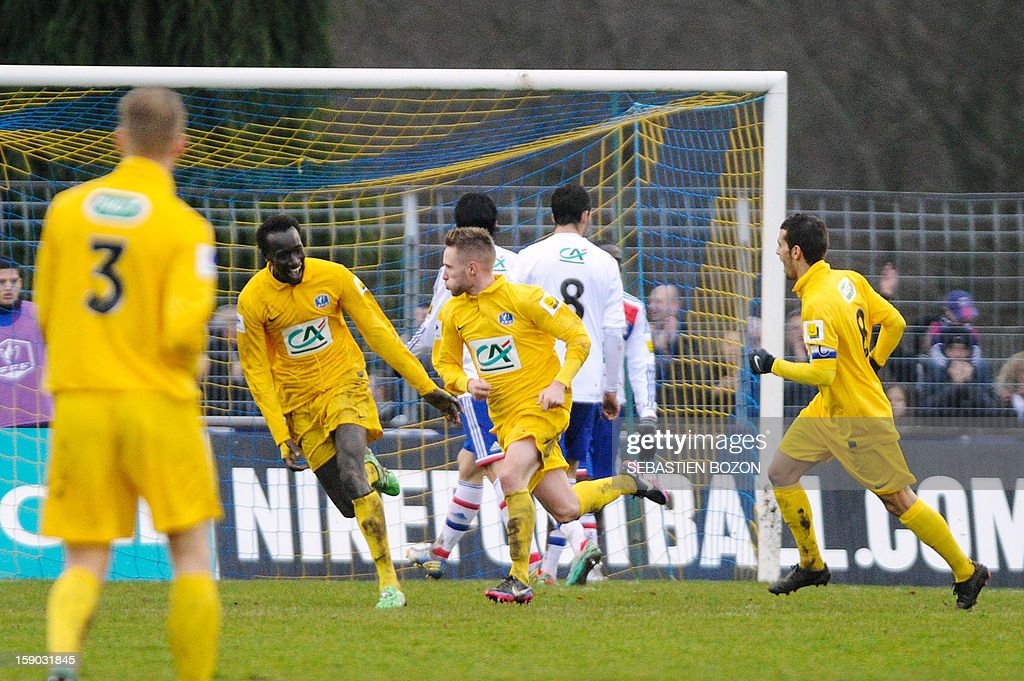 Epinal's French midfielder Valentin Focki (C) jubilates with teammates after scoring a goal during the French cup football match Epinal (SAS) versus Lyon (OL) at the Colombiere Stadium in Epinal, on January 6, 2013.
