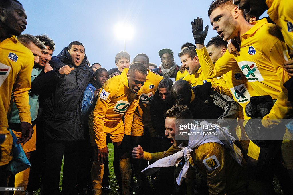 Epinal's players celebrate after winning a French Cup round of 64 football match against Lyon at the Colombiere Stadium in Epinal on January 6, 2013. AFP PHOTO / SEBASTIEN BOZON
