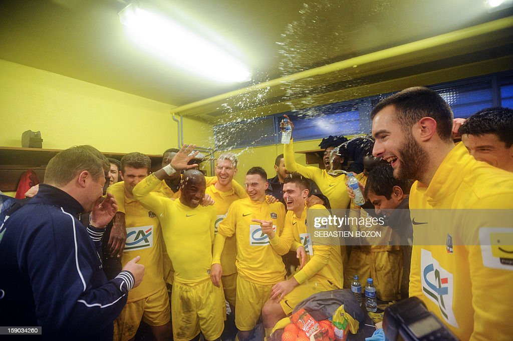 Epinal's players celebrate in their locker room after winning a French Cup round of 64 football match against Lyon at the Colombiere Stadium in Epinal on January 6, 2013.
