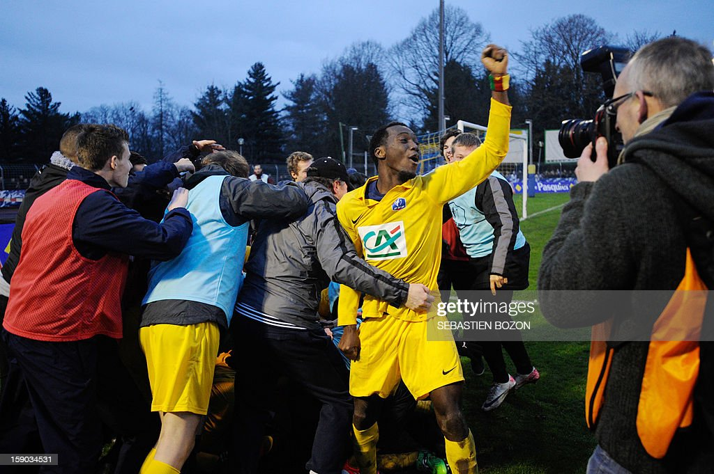 Epinal's players celebrate with supporters after beating Lyon during their French cup football match Epinal (SAS) vs Lyon (OL) at the Colombiere Stadium in Epinal, on January 6, 2013.