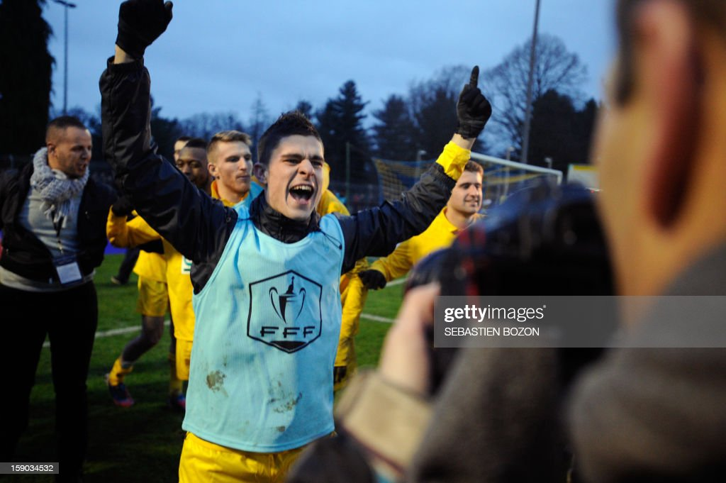 Epinal's players celebrate with supporters after beating Lyon during their French cup football match Epinal (SAS) vs Lyon (OL) at the Colombiere Stadium in Epinal, on January 6, 2013. AFP PHOTO / SEBASTIEN BOZON