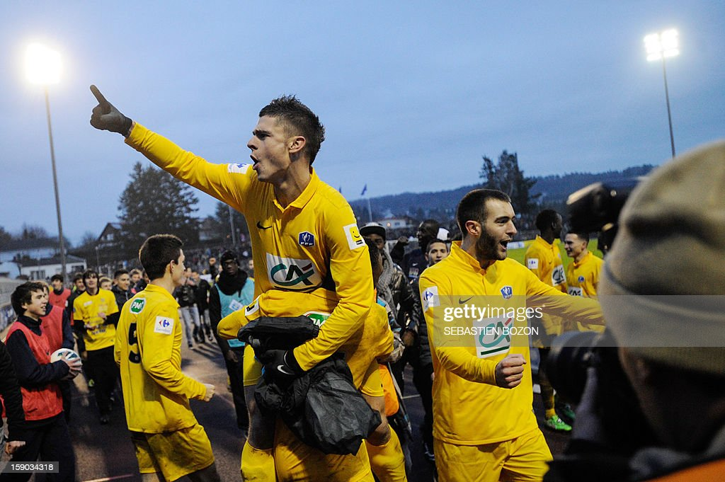 Epinal's players celebrate with supporters after winning a French Cup round of 64 football match against Lyon at the Colombiere Stadium in Epinal on January 6, 2013.