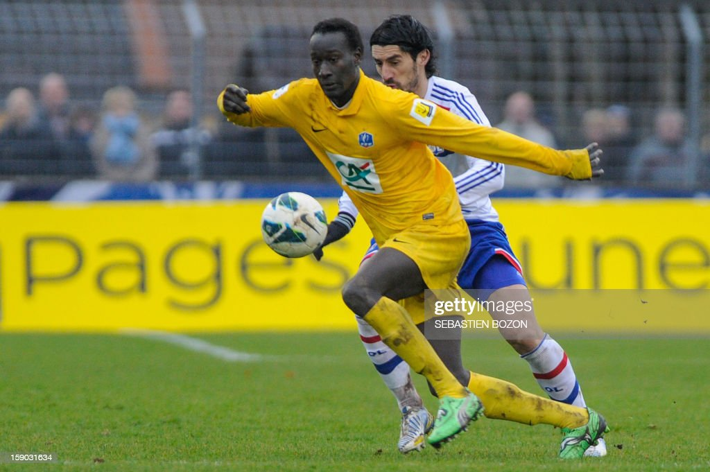 Epinal's Senegalese forward Famara Diedhiou (C) vies with Lyon's Serbian defender Milan Bisevac (R) during a French Cup football match between Epinal (SAS) and Lyon (OL) at the Colombiere Stadium in Epinal on January 6, 2013.