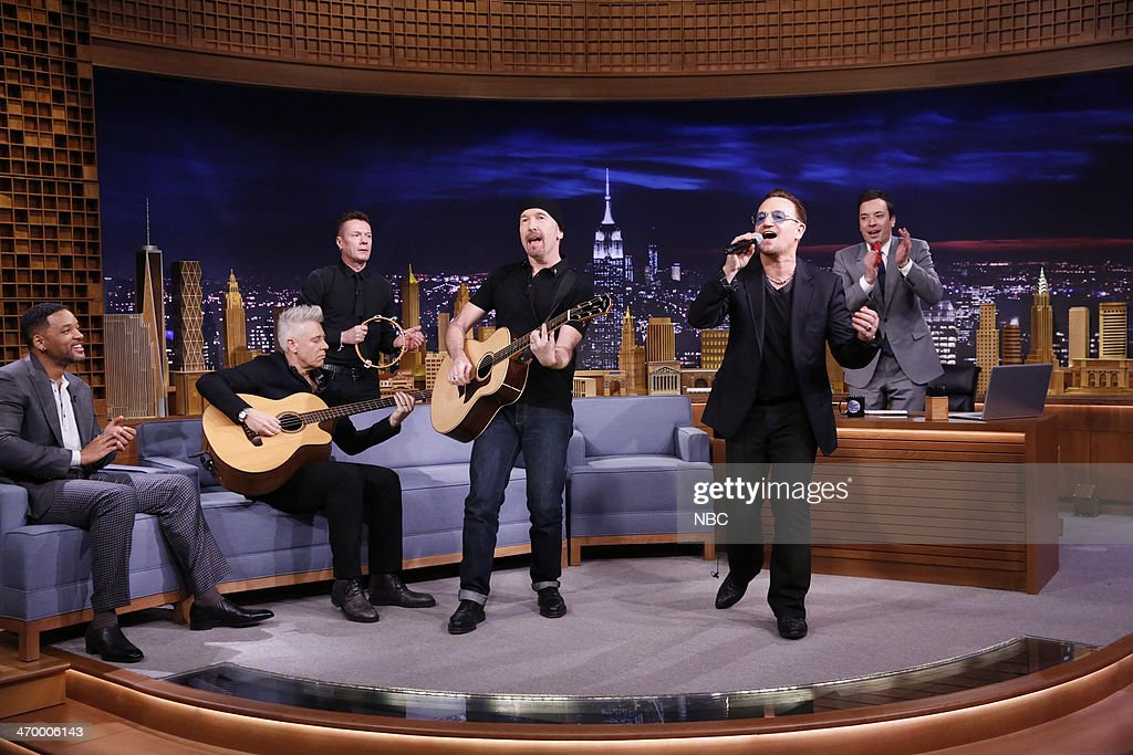 Adam Clayton Larry Mullen Jr The Edge and Bono of musical guest U2 perform as host Jimmy Fallon and actor Will Smith look on on February 17 2014