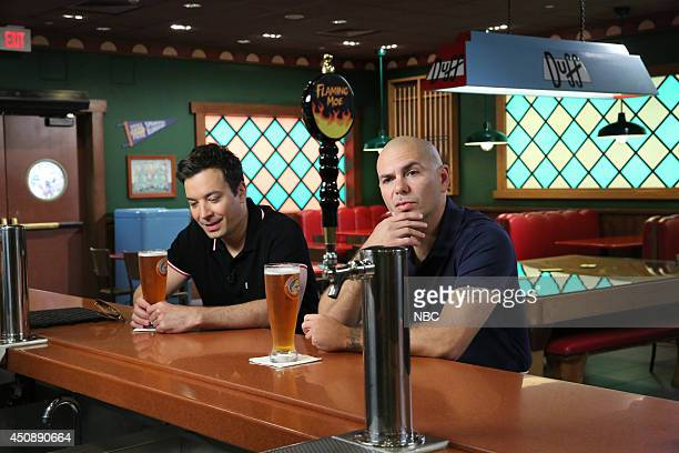 Host Jimmy Fallon and musical artist Pitbull play 'Giant Duff Beer Pong' on June 19 2014