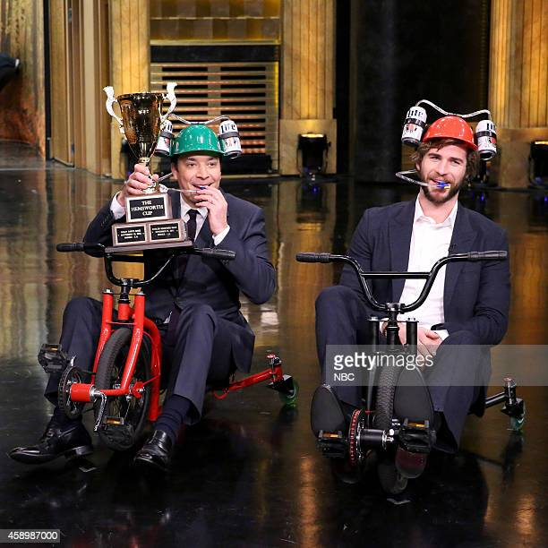 Host Jimmy Fallon and actor Liam Hemsworth compete in a giant tricycle race on November 14 2014