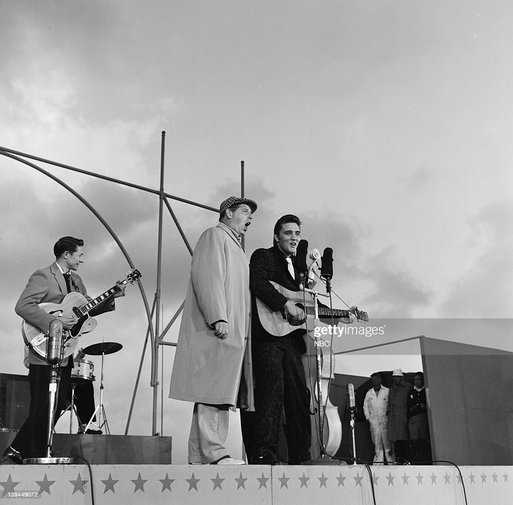 Guitarist Scotty Moore host Milton Berle Elvis Presley on the deck of the USS Hancock aircraft carrier