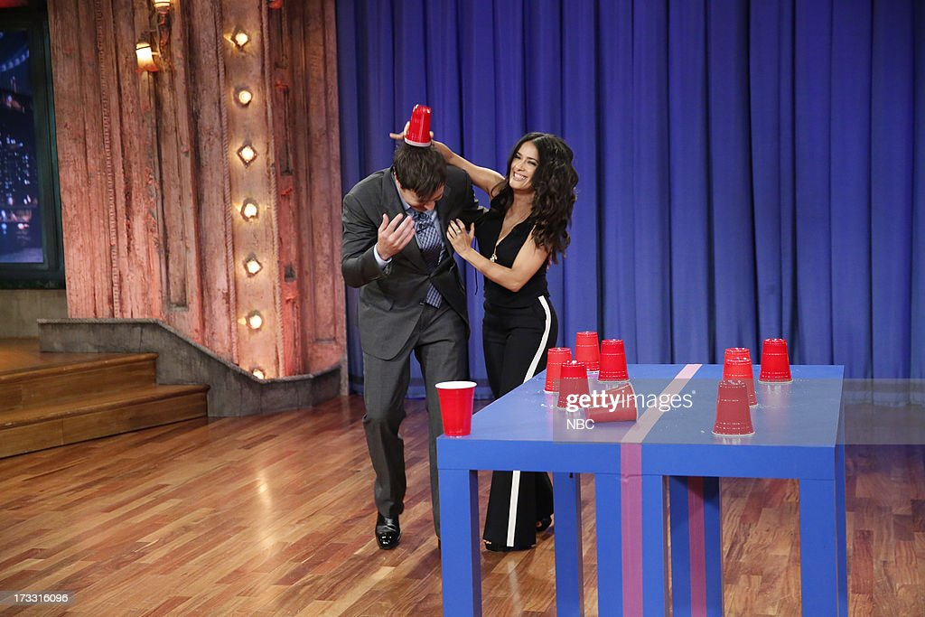 Host Jimmy Fallon with actress Salma Hayek Pinault during a game of 'Flip Cup' on the July 11, 2013 --