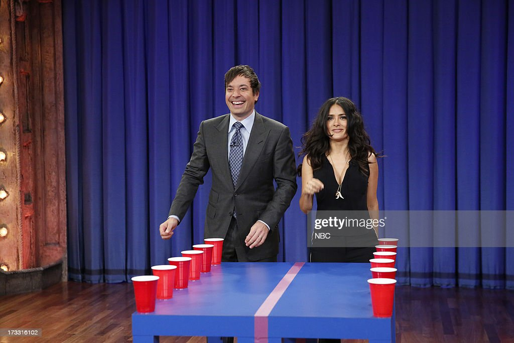 Host Jimmy Fallon with actress <a gi-track='captionPersonalityLinkClicked' href=/galleries/search?phrase=Salma+Hayek&family=editorial&specificpeople=201844 ng-click='$event.stopPropagation()'>Salma Hayek</a> Pinault during a game of 'Flip Cup' on the July 11, 2013 --