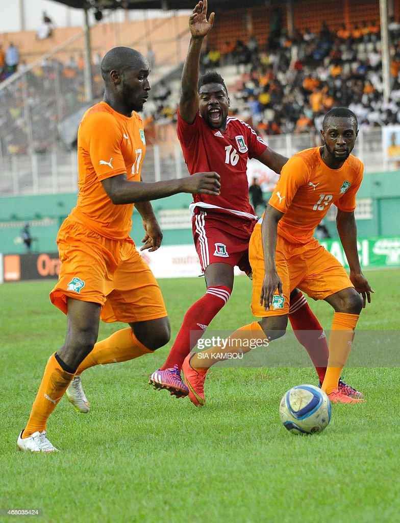 Equatorial Guinea's Armando Sipoto (C) vies with Ivory Coast's Jean-Daniel Akpa Akpro (R) and Sio Giovani during the friendly football match Ivory Coast againt Equatorial Guinea on March 29, 2015 in the Felix Houphouet Boigny stadium in Abidjan. The match ended in a 1-1 draw.