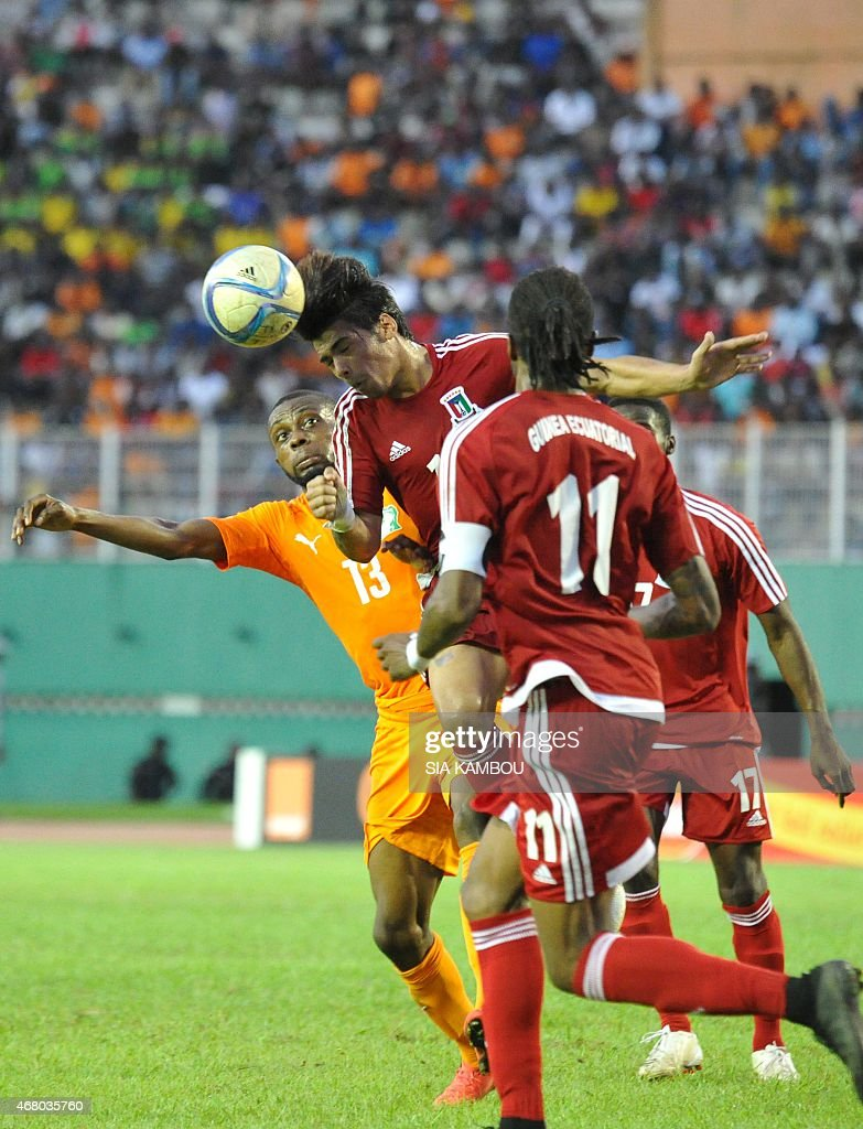 Equatorial Guinea's Carlos Akapo Martinez (C) vies with Ivory Coast's Jean Daniel Akpa Akpro during the friendly football match Ivory Coast againt Equatorial Guinea on March 29, 2015 in the Felix Houphouet Boigny stadium in Abidjan. The match ended in a 1-1 draw.