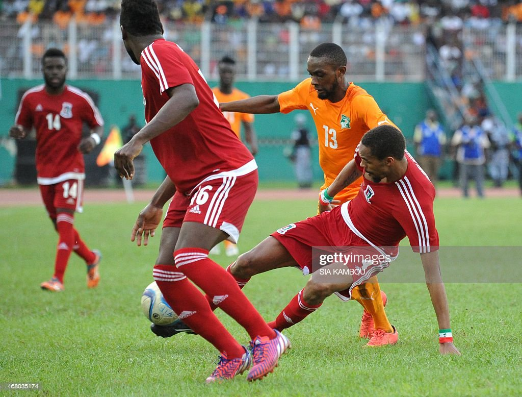 Equatorial Guinea's Fernando Rui Dangracia (C) Armando Sipoto Banale (L) vie with Ivory Coast's Jean-Daniel Akpa Akpro during the friendly football match Ivory Coast againt Equatorial Guinea on March 29, 2015 in the Felix Houphouet Boigny stadium in Abidjan. The match ended in a 1-1 draw.