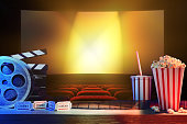Equipment and elements of cinema on wooden table and background cinema. Concept of watching movies. Horizontal composition. Front view.