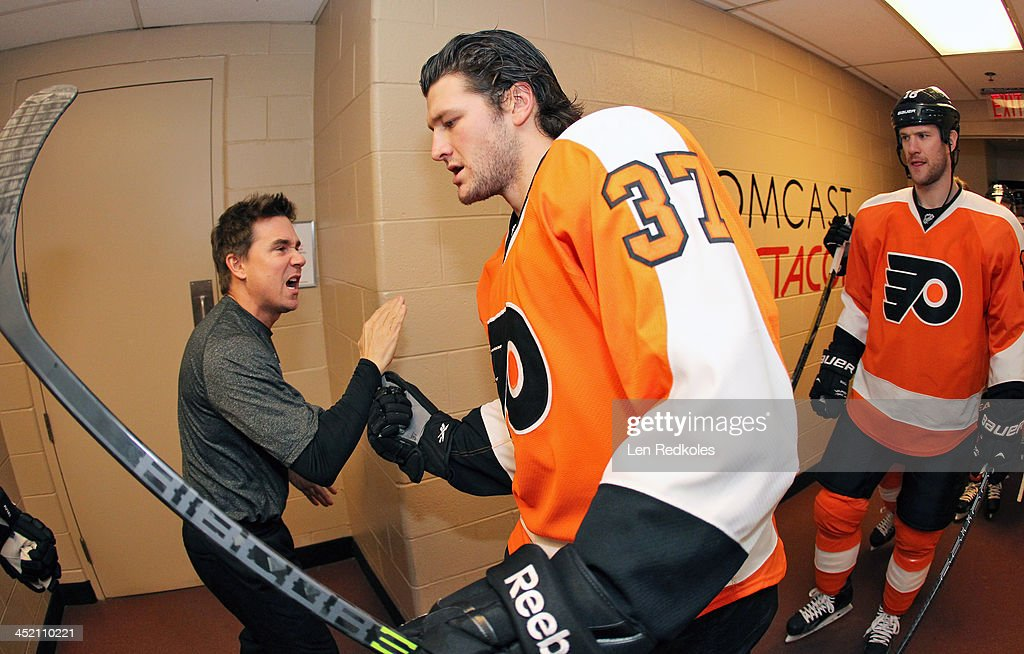 Equipment Manager Derek Settlemyre cheers on Jay Rosehill and Adam Hall of the Philadelphia Flyers prior to the start of their game against the...