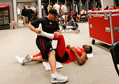 Equipment Manager Steve Urbaniak of the San Francisco 49ers stretches Michael Crabtree in the locker room prior to game against the Arizona Cardinals...