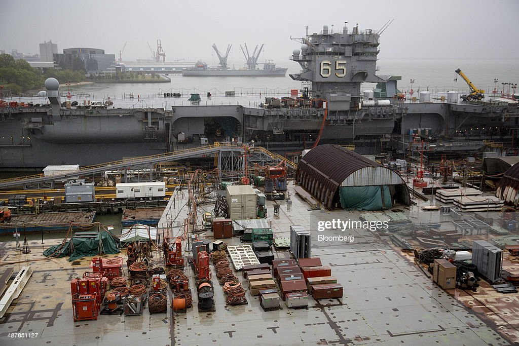 Equipment sits on the deck of the USS Gerald R Ford aircraft carrier during outfitting and testing as the USS Enterprise floats pier side during...