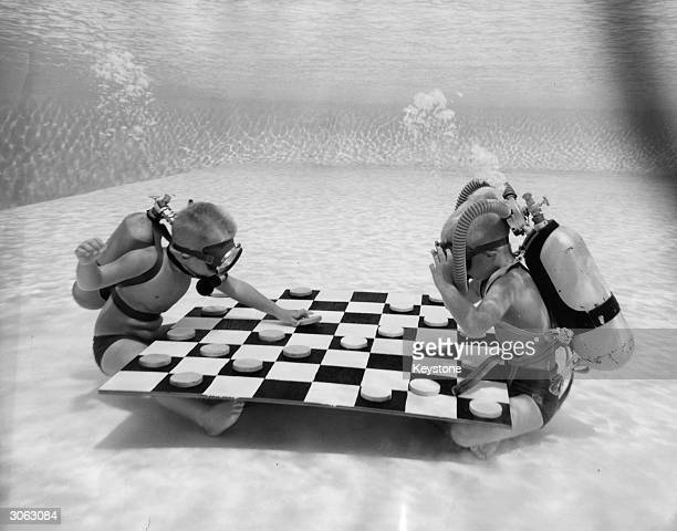 Equipped with masks and air cylinders six year olds Tom Lewis and George Baker play draughts at the bottom of a swimming pool in Winter Haven Florida