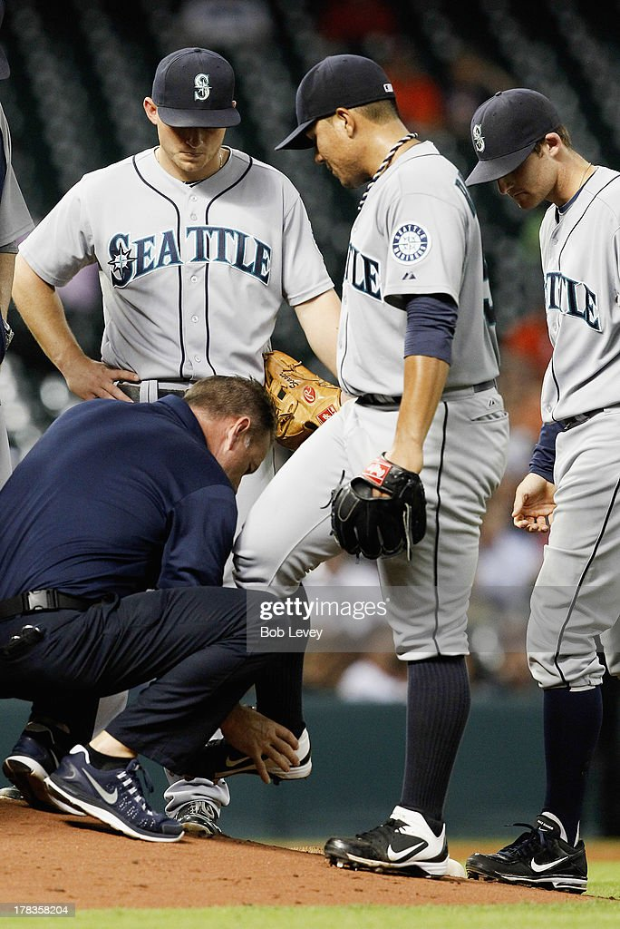Erasmo Ramirez #50 of the Seattle Mariners is looked at by the training staff after taking a line drive off his foot off the bat of Robbie Grossman #19 of the Houston Astros in the fifth inning at Minute Maid Park on August 29, 2013 in Houston, Texas.