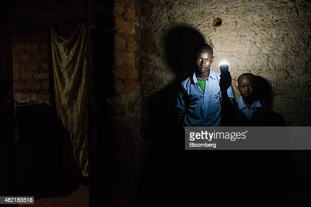 Erasmus Wambua a schoolboy left poses for a photograph holding an LED electric light powered by MKopa solar technology inside his home in Ndela...