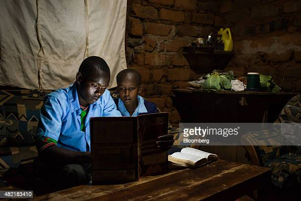 Erasmus Wambua a schoolboy left studies at home using a book illuminated by a single electric LED lightbulb powered by MKopa solar technology in...