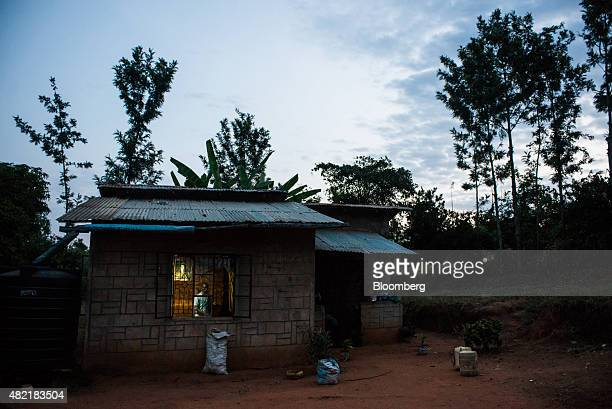 Erasmus Wambua a schoolboy looks at a single electric lightbulb as it illuminates his home powered by MKopa Solar technology in Ndela village...