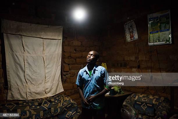 Erasmus Wambua a schoolboy looks at a single electric lightbulb powered by MKopa solar technology as it illuminates his home in Ndela village...