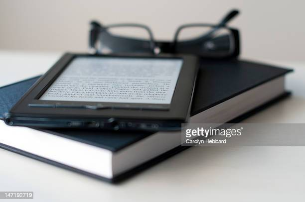 E-Reader and book with reading glasses
