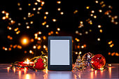 E-reader on flat surface, christmas them, blurred backgrund, rich colors