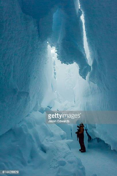 A photographer examines the frozen ceiling and icy walls of an ice cave in the Erebus Glacier Tongue.