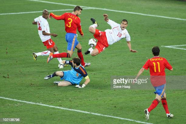 Eren Derdiyok of Switzerland jumps over Iker Casillas of Spain as he rushes out of his goal which leads up Gelson Fernandes to score during the 2010...