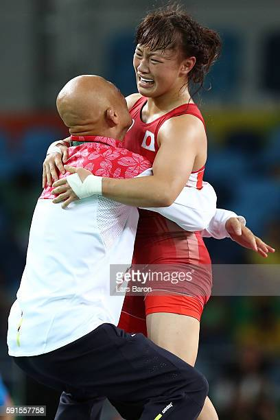 Eri Tosaka of Japan celebrates winning gold with coach Kazuhito Sakai over Mariya Stadnik of Azerbaijan in the Women's Freestyle 48kg event on Day 12...